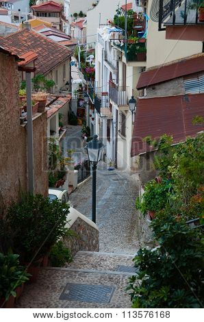 Narrow street and stairs between cute italian houses in old town of Scilla
