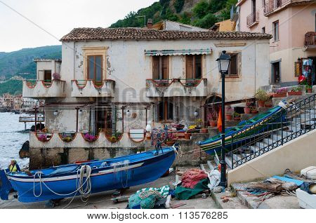 Blue and green boat in front of a house in the small italian town Scilla
