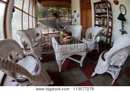 White rattan furniture on tiled floor in a hostel