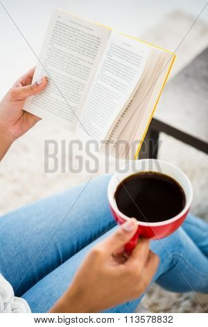 Cropped image of woman with coffee reading book at home