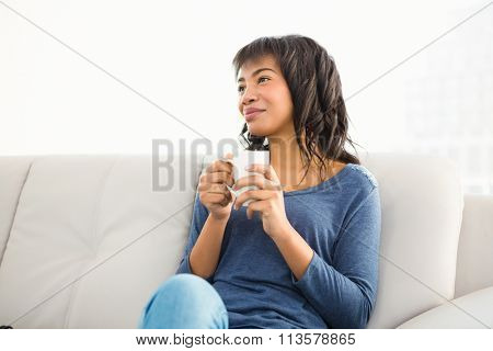Smiling casual woman holding coffee and looking otherwise at home