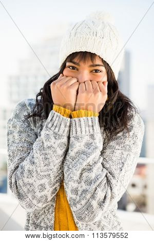 Smiling woman wearing winter clothes with hands on mouth outside