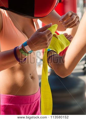 Close Up Of Young Girls Taping Her Hands In Pink Boxing Tape