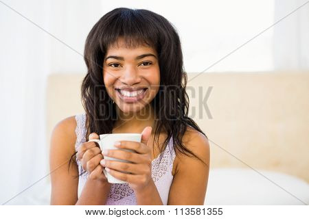Casual smiling woman holding a cup of coffee at home