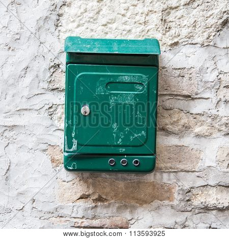 Old Green Mailbox Attached To A Stone Wall.