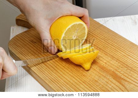 Hand With A Knife Cuts A Lemon Into Slices