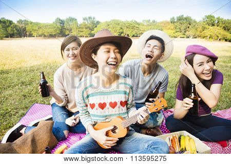 Happy Young Friends Enjoying Picnic And Playing Ukulele