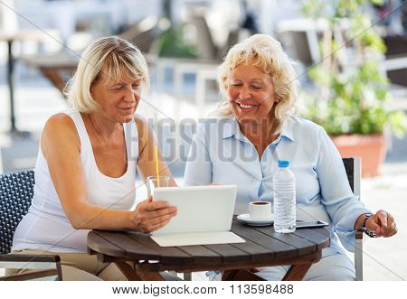 Female friends watching something on tablet PC in cafe