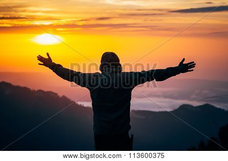 Man Traveler hands raised silhouette outdoor with sunset sky mountains on background