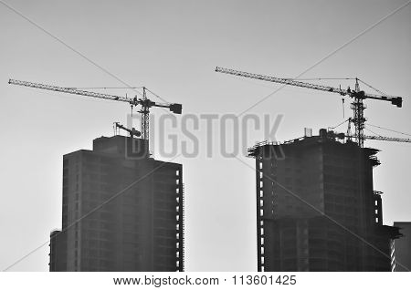 Two Buildings And Cranes