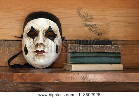 venetian mask and books on a shelf