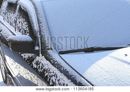 The window of the car with snow and wipers on a sunny day in winter.