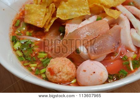 noodles with fish ball and red sauce in soup