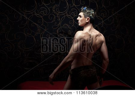 Handsome Man Wearing Crown Standing On A Bed.