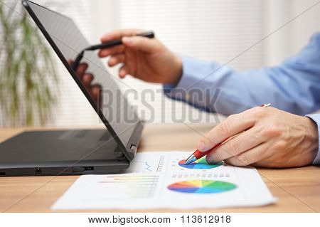 Businessman Is Analyzing Business Data  On Document And Working With  Stylus Pen On Touchscreen Lapt