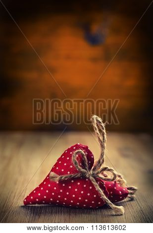 Valentines day. Wedding day. Red cloth handmade hearts on wooden background - table. Free space for