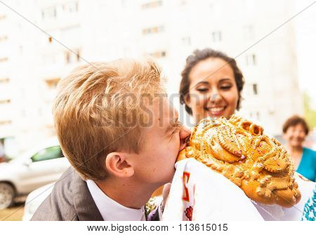 Closeup photo of bride and groom nibbling traditional loaf