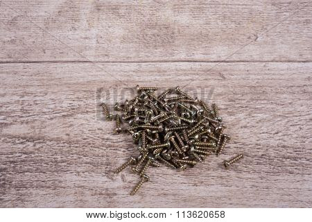 Many Brass Screws Lying On Wooden Table- Close Up