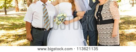newly married couple embracing with parents standing in the background