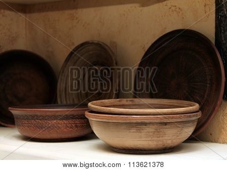 Clay plates on a shelf close-up