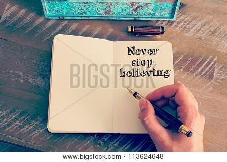 Motivational Message Never Stop Believing Written On Notebook