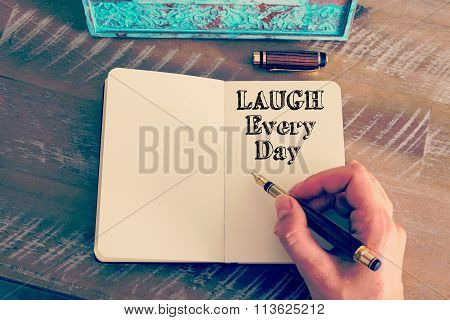 Motivational Message Laugh Every Day Written On Notebook