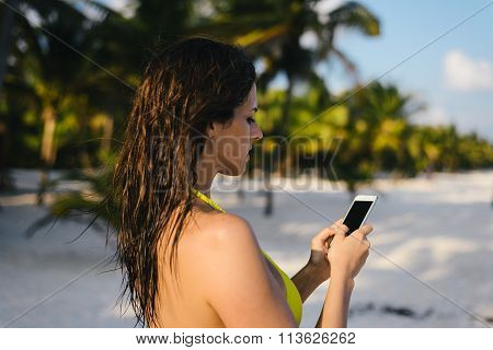 Woman Texting On Smartphone At Tropical Caribbean Beach