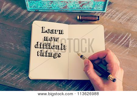 Motivational Message Learn New Difficult Things Written On Notebook