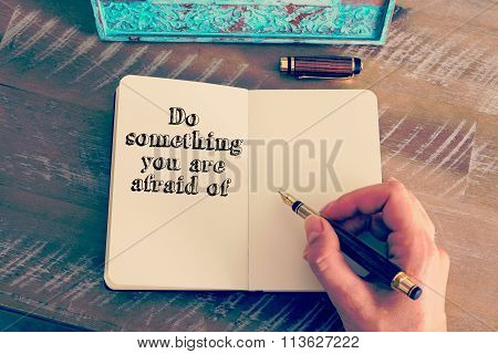Motivational Message Do Something You Are Afraid Of Written On Notebook
