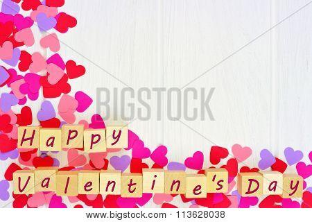 Valentines Day blocks with heart corner border against white wood