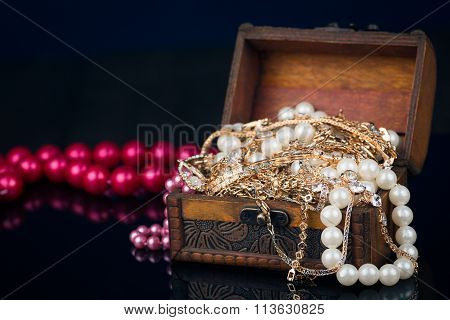 Chest with jewels on dark background