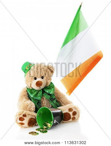 A toy bear sitting in a St. Patrick's Day outfit.  An Irish flag flies behind him and a bucket of gold coins are spilled in front.  On a white background.