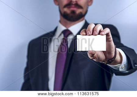 Bearded man in dark suit holds business card