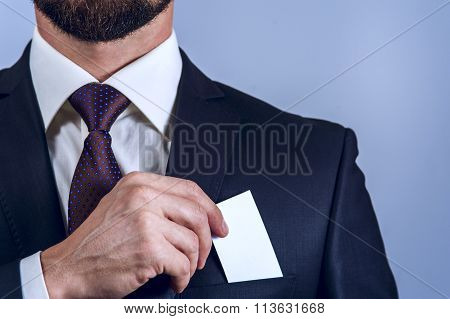 Bearded man in dark suit removes card to pocket