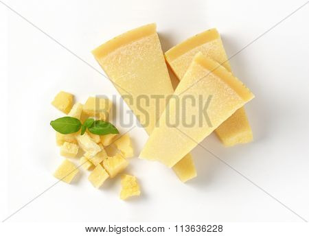 wedges and pieces of parmesan cheese on white background