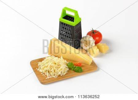 grater and heap of grated parmesan cheese on wooden cutting board