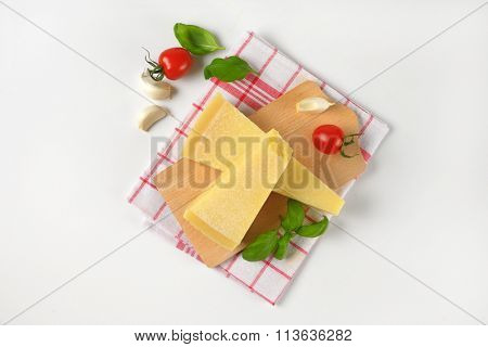 wedges of fresh parmesan cheese and vegetable garnish on wooden cutting board