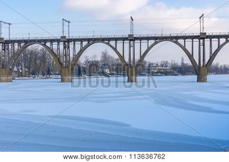Arched bridge on winter river Dnepr
