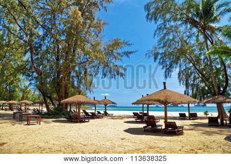 Wooden chairs and umbrellas on white sand beach at Koh Chang island in Thailand