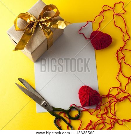 Two knitted hearts, gift box and scissors