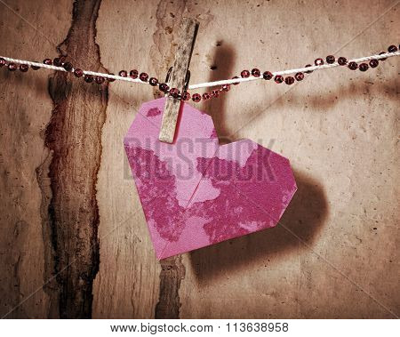 Broken red heart hung on rope.