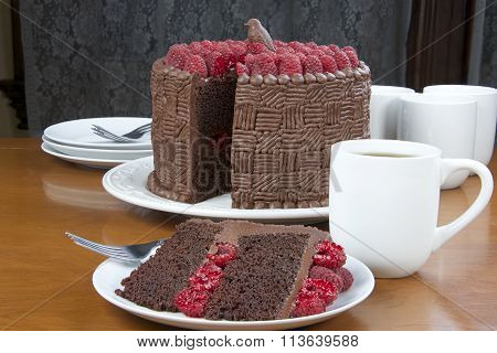 Slice of Home made original design chocolate cake with fresh raspberry filling raspberries on top