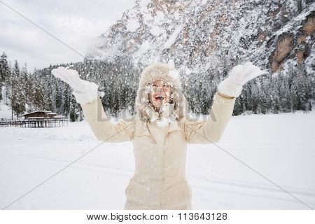 Happy Woman In Fur Hat Throwing Up Snow While Standing Outdoos