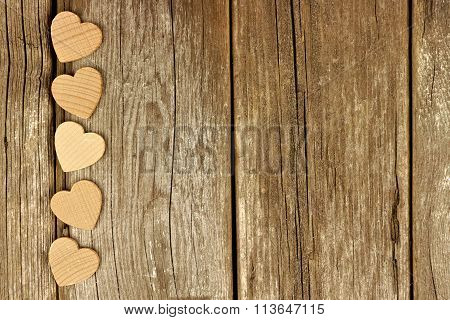 Valentines Day wooden hearts bottom border on rustic wood