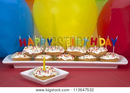 Miniature donut cake on long rectangular cake with single donut on square plate yellow candle