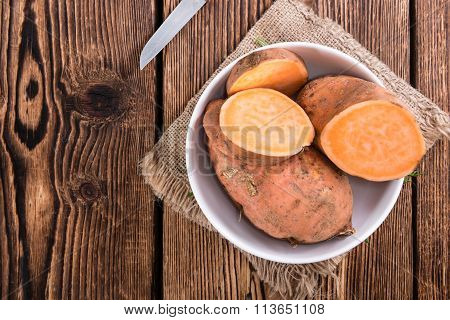 Sweet Potato (uncooked) On Wooden Background