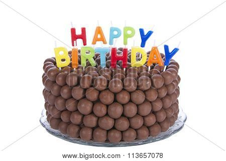 Chocolate cake decorated with rows of candy malt balls with happy birthday candles isolated on white