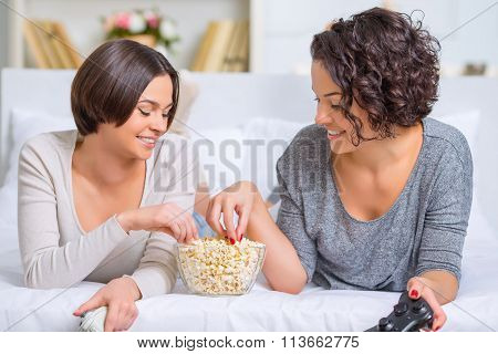 Sisters eating popcorn between videogames.