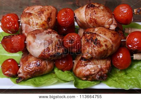 Grilled Barbecue Kebab Chicken Legs And Tomatoes On Skewers