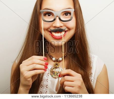 woman holding mustache and glasses on a stick
